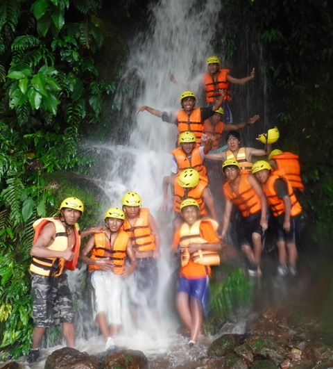 The whole group posing at a waterfall after rafting through the pouring rain on a swollen river